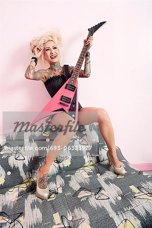 Cheerful young woman sitting on furniture with guitar Stock Photo - Premium Royalty-Free, Image code: 693-06323927