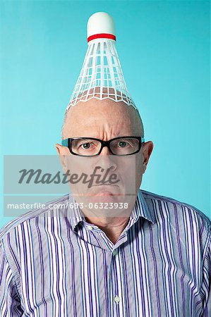 Portrait of angry man with shuttlecock on head over colored background Stock Photo - Premium Royalty-Free, Image code: 693-06323938
