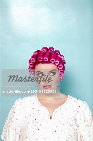 Young woman with curlers on pink hair over colored background Stock Photo - Premium Royalty-Free, Image code: 693-06323939
