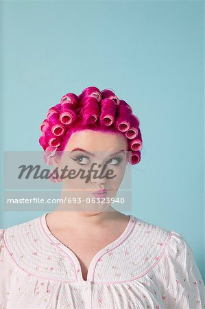 Young woman making faces with pink hair and curlers over colored background Stock Photo - Premium Royalty-Free, Image code: 693-06323940
