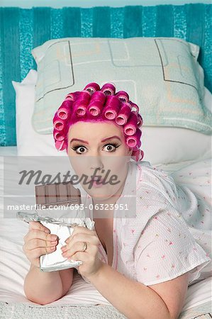 Portrait of shocked woman lying on bed with chocolate bar Stock Photo - Premium Royalty-Free, Image code: 693-06323951