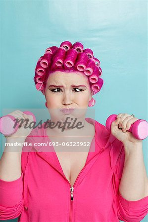 Young woman crossed eyes lifting dumbbell over colored background Stock Photo - Premium Royalty-Free, Image code: 693-06323952