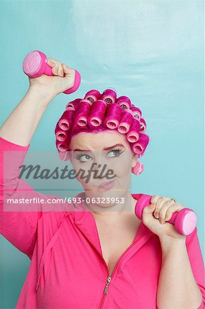 Young woman making face while lifting dumbbell over colored background Stock Photo - Premium Royalty-Free, Image code: 693-06323953