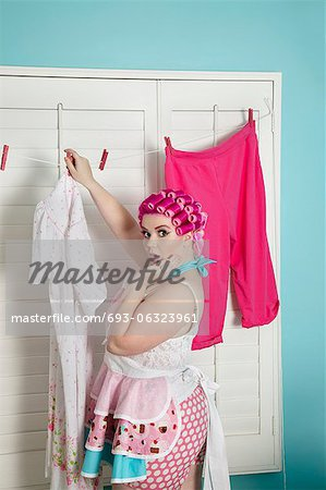 Portrait of a shocked plus-size woman drying clothes Stock Photo - Premium Royalty-Free, Image code: 693-06323961