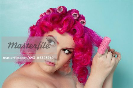 Young woman removing hair curlers over colored background Stock Photo - Premium Royalty-Free, Image code: 693-06323962