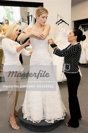 Mother and store employee assisting young woman getting dressed in bridal store Stock Photo - Premium Royalty-Free, Image code: 693-06324061