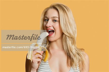 Portrait of a beautiful blond woman eating banana over colored background Stock Photo - Premium Royalty-Free, Image code: 693-06324131