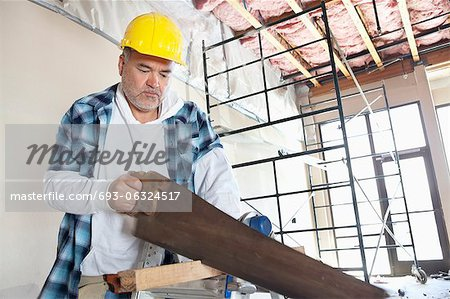 Serious male construction worker cutting wood with handsaw Stock Photo - Premium Royalty-Free, Image code: 693-06324517