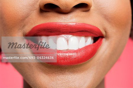 Close-up detail of an African American woman smiling over colored background Stock Photo - Premium Royalty-Free, Image code: 693-06324636