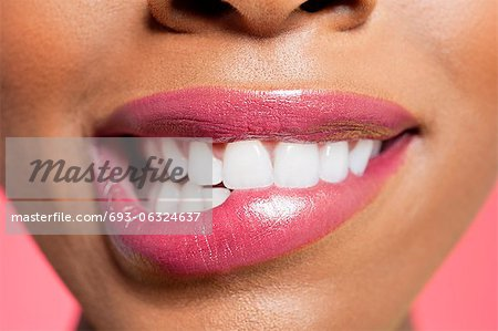 Close-up view of an female biting her lip over colored background Stock Photo - Premium Royalty-Free, Image code: 693-06324637