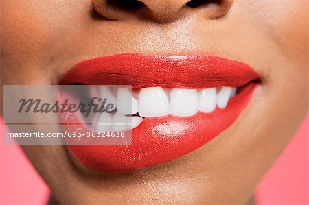 Close-up view of an female biting her red lip over colored background Stock Photo - Premium Royalty-Free, Image code: 693-06324638