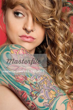 Beautiful young woman looking sideways with tattooed arm Stock Photo - Premium Royalty-Free, Image code: 693-06324651