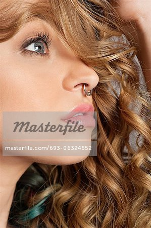 Close-up of beautiful blond woman with pierced nose looking away Stock Photo - Premium Royalty-Free, Image code: 693-06324652