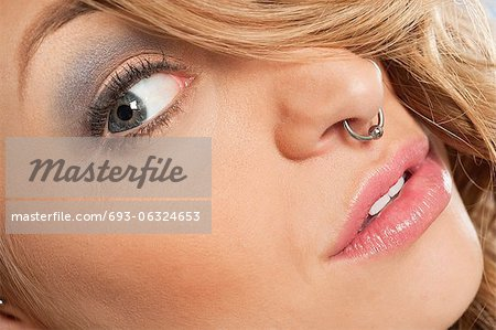 Cropped image of beautiful young woman with nose ring looking sideways Stock Photo - Premium Royalty-Free, Image code: 693-06324653