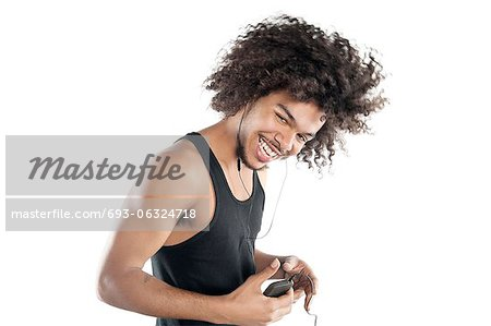 Portrait of a happy young man with mp3 player over white background