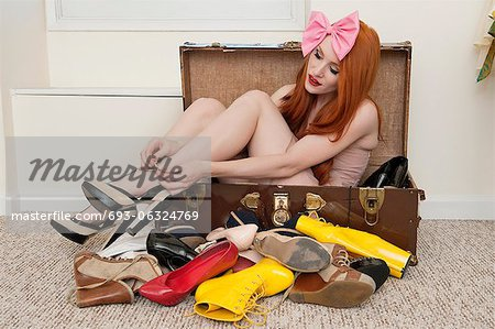 Young woman with bow headband tying footwear while sitting in suitcase Stock Photo - Premium Royalty-Free, Image code: 693-06324769