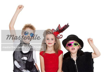 Portrait of kids fancy dress outfit with raised fist over white background Stock Photo - Premium Royalty-Free, Image code: 693-06324841