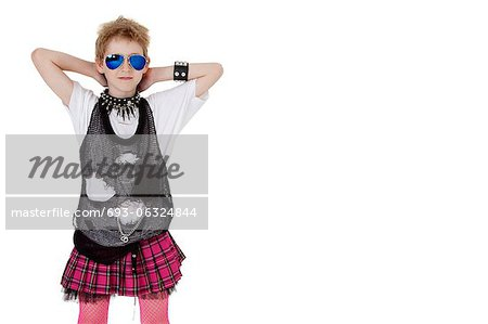 Portrait of punk kid in fancy dress with hands behind head over white background Stock Photo - Premium Royalty-Free, Image code: 693-06324844