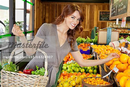 Portrait of a happy young female shopping for fruits in market Stock Photo - Premium Royalty-Free, Image code: 693-06324907