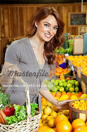 Portrait of a happy young woman shopping in market for fruits Stock Photo - Premium Royalty-Free, Image code: 693-06324909
