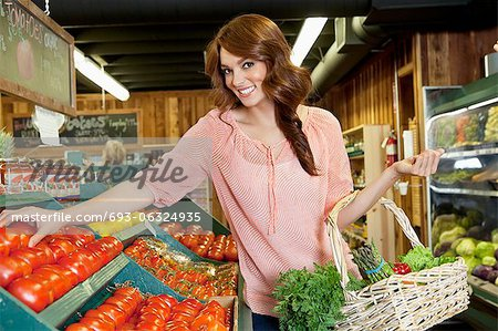 Portrait of a happy brunette shopping for tomatoes in supermarket Stock Photo - Premium Royalty-Free, Image code: 693-06324935