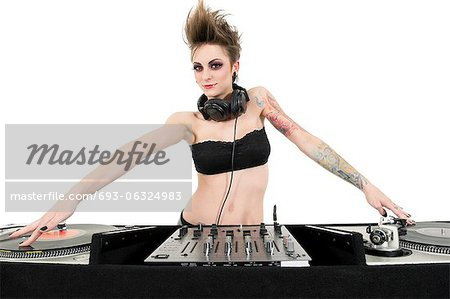 Portrait of beautiful young female DJ wearing strapless lingerie over white background