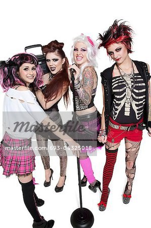 Portrait of young rock band of females with microphone and boom box over white background