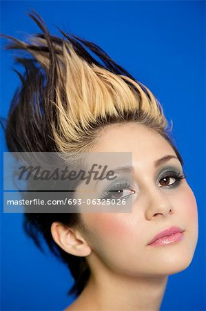 Close-up portrait of beautiful young woman with spiked hair over blue background Stock Photo - Premium Royalty-Free, Image code: 693-06325026