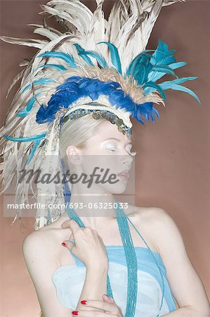 Beautiful young woman wearing feather headgear with eyes closed Stock Photo - Premium Royalty-Free, Image code: 693-06325033