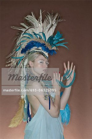Portrait of young woman in feathered outfit over colored background Stock Photo - Premium Royalty-Free, Image code: 693-06325035