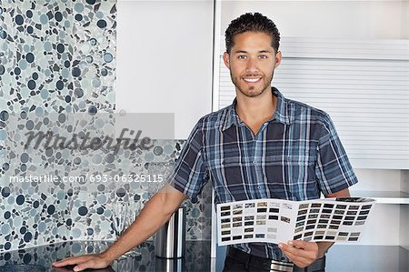 Portrait of young man with color samples standing in model home kitchen Stock Photo - Premium Royalty-Free, Image code: 693-06325115