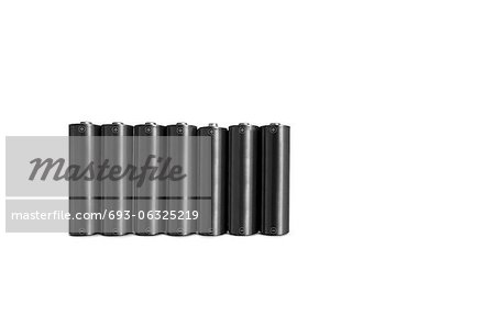 Close-up of black batteries over white background Stock Photo - Premium Royalty-Free, Image code: 693-06325219