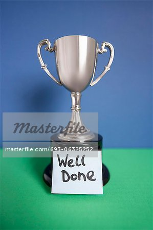 Winning trophy award with sticky note over colored background Stock Photo - Premium Royalty-Free, Image code: 693-06325252