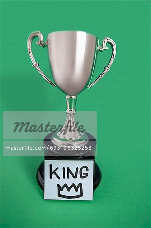 Trophy with sticky note over colored background Stock Photo - Premium Royalty-Free, Image code: 693-06325253