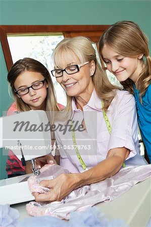 Girls looking grandmother sewing cloth Stock Photo - Premium Royalty-Free, Image code: 693-06378763