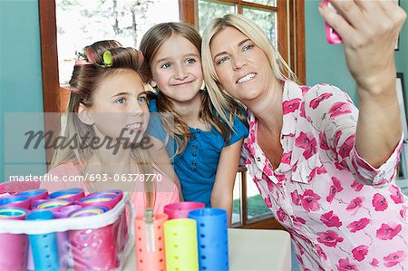 Mother with daughters taking self portrait with cell phone Stock Photo - Premium Royalty-Free, Image code: 693-06378770