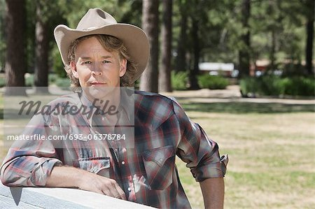 Portrait of a mature man wearing cowboy hat leaning on wooden slab Stock Photo - Premium Royalty-Free, Image code: 693-06378784