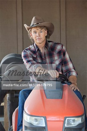 Portrait of a cowboy driving utility vehicle Stock Photo - Premium Royalty-Free, Image code: 693-06378795