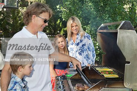 Family of four barbecuing Stock Photo - Premium Royalty-Free, Image code: 693-06378801