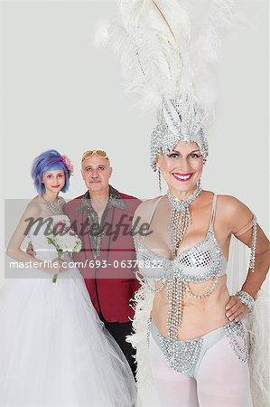 Portrait of senior showgirl with father and daughter in wedding dress against gray background Stock Photo - Premium Royalty-Free, Image code: 693-06378822