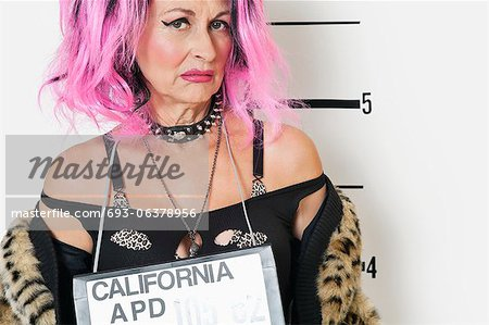 Portrait of senior punk woman making a face during mug shot Stock Photo - Premium Royalty-Free, Image code: 693-06378956