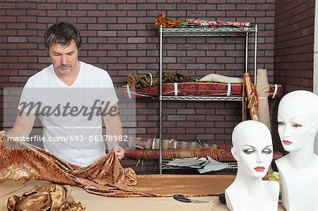 Mature male fashion designer working on cloth in design studio Stock Photo - Premium Royalty-Free, Image code: 693-06378982