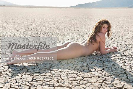 Naked young woman lying on cracked arid landscape Stock Photo - Premium Royalty-Free, Image code: 693-06379201