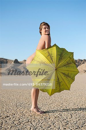Portrait of a happy naked woman with yellow umbrella on barren landscape Stock Photo - Premium Royalty-Free, Image code: 693-06379210