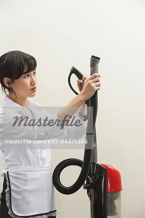 Female housekeeper holding vacuum cleaner pipe against gray background Stock Photo - Premium Royalty-Free, Image code: 693-06379356