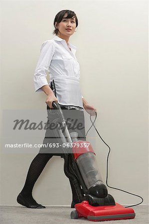 Full length of young female housekeeper vacuuming Stock Photo - Premium Royalty-Free, Image code: 693-06379357