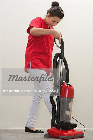 Full length of female housekeeper using vacuum cleaner Stock Photo - Premium Royalty-Free, Image code: 693-06379358