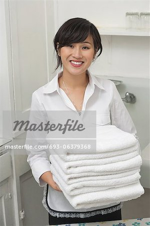Portrait of young female housekeeper holding clean white folded towels Stock Photo - Premium Royalty-Free, Image code: 693-06379368
