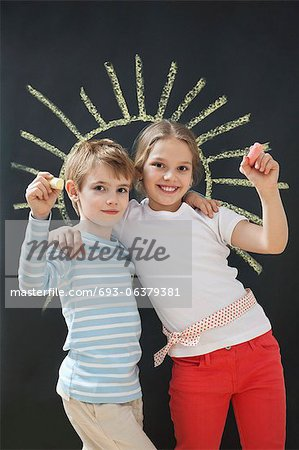 Portrait of happy siblings holding chalks against blackboard Stock Photo - Premium Royalty-Free, Image code: 693-06379381