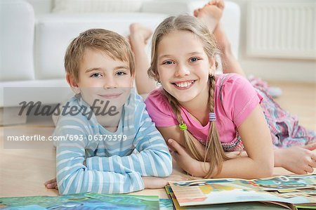 Portrait of happy brother and sister with story books while lying on floor Stock Photo - Premium Royalty-Free, Image code: 693-06379399